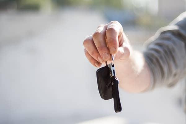 man in grey shirt handing over car key